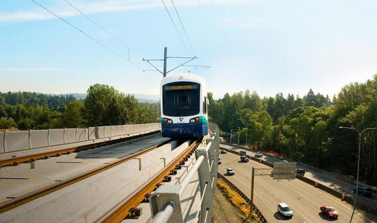 Light rail train traveling on tracks adjacent to highway.